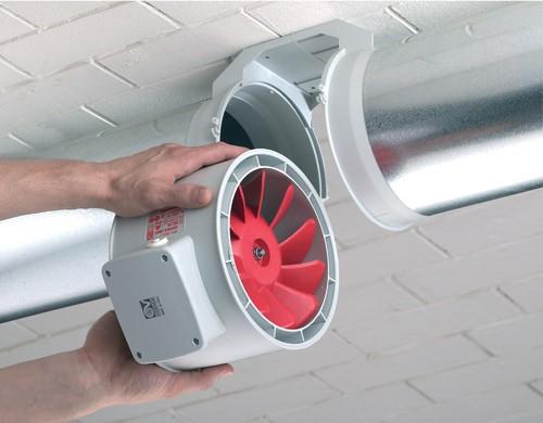 Мужчина устанавливает канальный вентилятор для вытяжки