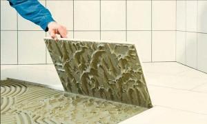 Мужчина кладет плитки в ванной