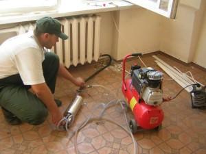 Работник промывает систему отопления