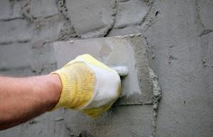 Мужчина наносит цемент на стену