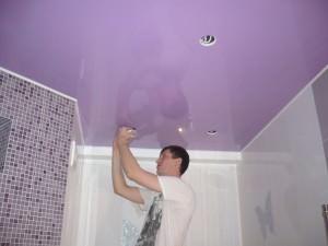 Мужчина устанавливает светильники в ванной