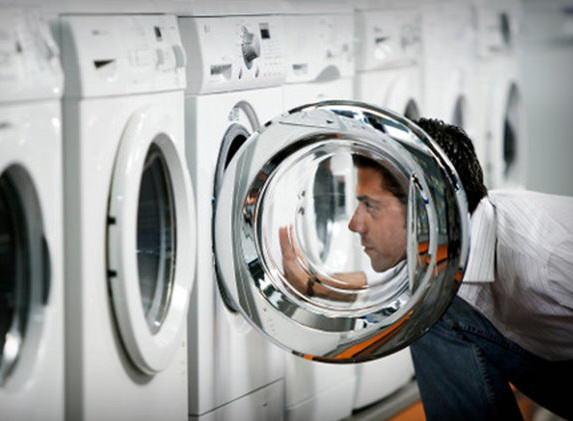Мужчина заглядывает в стиральную машину